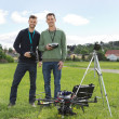 Engineers Standing By UAV Helicopter And Tripod — Stock Photo #31869467