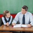 Stock Photo: Professor And Little Girl Looking At Each Other At Desk
