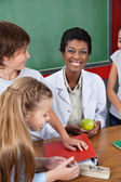 Teacher Holding Apple With Students Standing At Desk — Stock Photo
