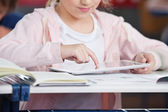 Midsection Of Schoolgirl Using Tablet At Desk — Stock Photo