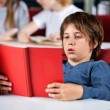 Relaxed Boy Reading Book At Table In Library — Stock Photo #31911981