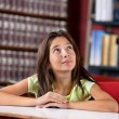 Thoughtful Schoolgirl Looking Up In Library — Stock Photo #31912449