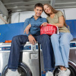 Couple With Clothes Basket Sitting On Washing Machine — Stockfoto