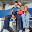 Couple With Clothes Basket Sitting On Washing Machine — Foto de Stock