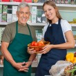 Saleswoman Holding Vegetable Basket With Male Colleague In Groce — Stock Photo