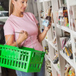 Woman With Shopping Basket Choosing Product — Stock Photo #31977699