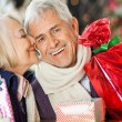 Woman About To Kiss Man Holding Christmas Presents — Stock Photo