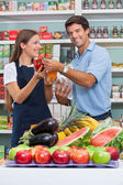 Male Customer With Saleswoman Comparing Bellpepper At Supermarke — Stock Photo