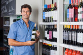 Man Holding Bottle Of Alcohol At Supermarket — Stock Photo