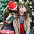 Man Surprising Woman With Christmas Presents In Store — Stock Photo