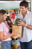 Couple Putting Bellpepper And Pumpkin In Paper Bag — Stock Photo