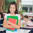 Schoolgirl Holding Books While Standing At Desk — Stock Photo