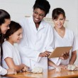 Teacher Looking At Schoolgirls While Using Tablet In Biology Cla — Stock Photo