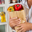 Stock Photo: MHolding Bag Of Vegetables In Store