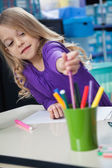 Girl Picking Sketch Pen From Case In Classroom — Stock Photo