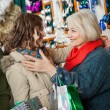 Affectionate Mother And Daughter Embracing At Christmas Store — Stock Photo #32070389