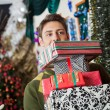Stock Photo: Man Carrying Stacked Christmas Gifts In Store