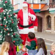 Stock Photo: Children With Presents Looking At Santa Claus
