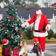 Santa Claus Gesturing At Children By Christmas Tree — Stock Photo