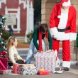 Santa Claus And Girl Looking At Boy Opening Gift — Stock Photo