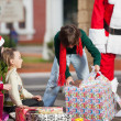 Boy Opening Christmas Present In Courtyard — Stock Photo #32073805
