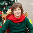 Boy Sitting On Chair Against Christmas Tree — Stock Photo