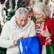 Stock Photo: Surprised Couple Looking Into Shopping Bag