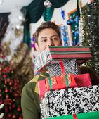 Hombre que llevaba apilados regalos de Navidad en la tienda — Foto de Stock