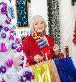 Bella mujer con bolsas de la compra en tienda — Foto de Stock