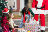 Boy Opening Christmas Present In Courtyard — ストック写真