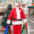 Santa Claus Carrying Shopping Bags In Courtyard — Stock Photo #32277961