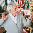 Man Buying Christmas Ornaments At Store — Stock Photo
