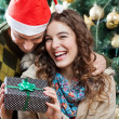Cheerful Couple With Christmas Present In Store — Stock Photo