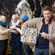 Man Pointing At Christmas Present With Family In Background — Foto de Stock