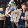 Man Pointing At Christmas Present With Family In Background — Stock Photo
