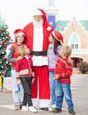 Weihnachtsmann mit kindern stehen im innenhof — Stockfoto