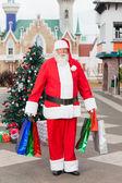 Santa claus bär kassar på innergården — Stockfoto