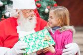 Santa claus geben weihnachtsgeschenk für mädchen — Stockfoto