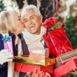 Woman Kissing Man Holding Christmas Presents — Stock Photo