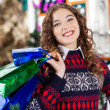 Young Woman Carrying Shopping Bags In Christmas Store — Stock Photo