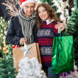 Couple With Shopping Bags Standing At Christmas Store — Stock Photo