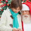 图库照片: Boy Showing Smartphone To Santa Claus