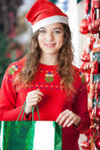 Woman In Santa Hat Carrying Shopping Bag — Stock Photo