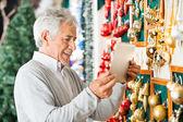 Glücklicher mann fotografieren christbaumschmuck im store — Stockfoto