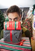 Mann sucht über gestapelte weihnachtsgeschenke im speicher — Stockfoto