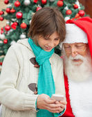 Boy Showing Smartphone To Santa Claus — Stock Photo