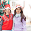 Friends In Santa Hat Standing Against Christmas Tree — Stock Photo