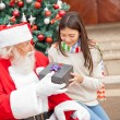 Girl Taking Christmas Gift From Santa Claus — Stock Photo #32971011