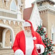 Santa Claus Putting Gift In Bag Outside House — Stock Photo