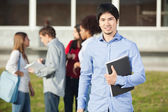 Man Holding Book With Students In Background On Campus — Stock Photo